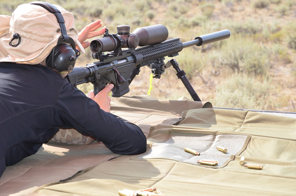 man holding a rifle with scope